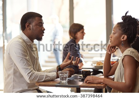 African entrepreneur explaining his idea to a businesswoman - stock photo