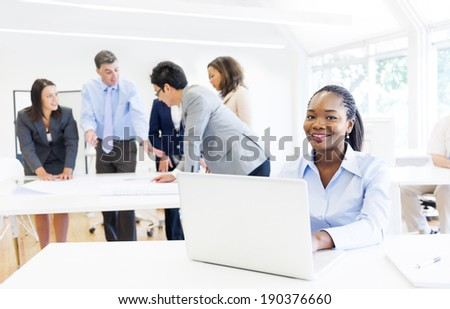 African ethnic woman smiling at the camera while working on her laptop with business meeting as the background. - stock photo