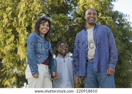 African family holding hands at park - stock photo