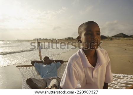 African father and son in hammock at beach