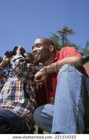 African father and son using binoculars - stock photo
