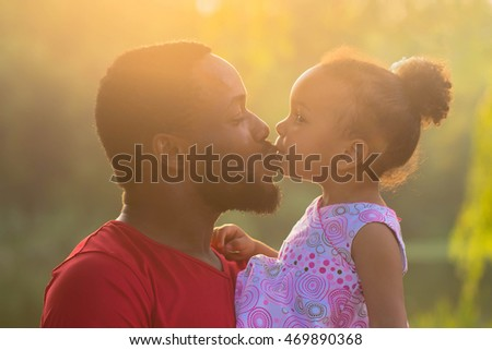 African father hugging and kissing a baby daughter. Happy fatherhood concept.
