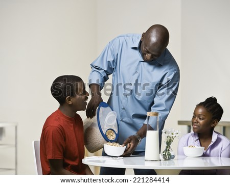 African father pouring cereal for son - stock photo