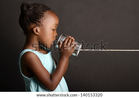 African girl communicating via a tin - stock photo