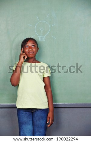 African girl having idea with lightbulb drawn on chalkboard in school - stock photo