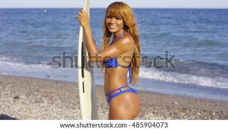 African Girl Holding Surfing Board at the Beach