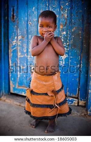 african girl in front of a blue door, vignette added for a dramatic effect.