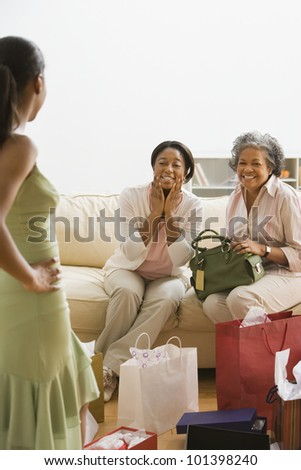 African girl modeling new dress for mother and grandmother - stock photo