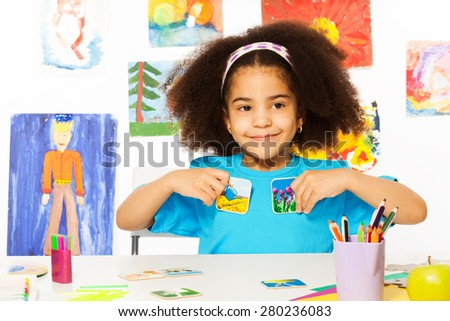 African girl plays developmental game, holds cards