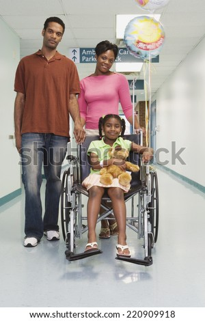 African girl smiling in wheelchair with parents in hospital - stock photo