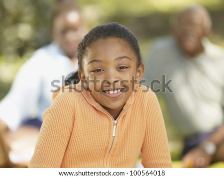 African girl smiling with family in background