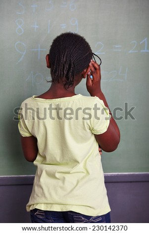 African girl solving math problem at blackboard in school - stock photo