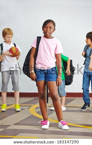 African girl standing with knapsack on schoolyard in elementary school - stock photo