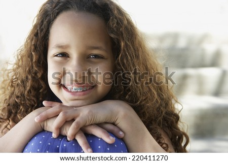 African girl with braces leaning chin on knees outdoors - stock photo