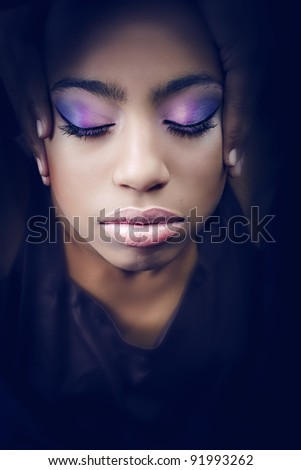 African girl with purple makeup and closed eyes