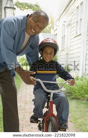 African grandfather teaching grandson to ride bicycle - stock photo