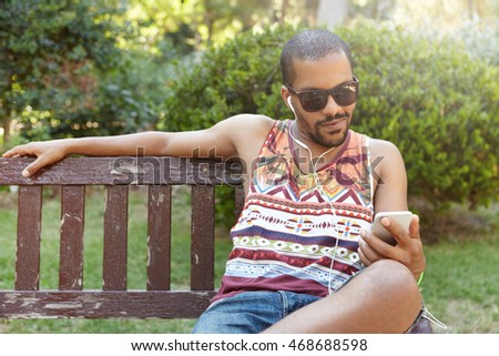 African guy in earphones sitting on bench in city park listening to music on his smartphone, checking e-mail using Internet-enabled mobile phone, liking posts and leaving comments on social networks