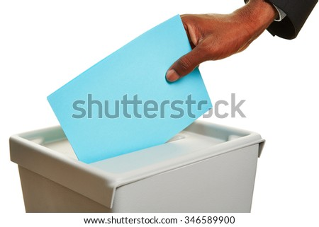 African hand with ballot paper at ballot box during an election - stock photo