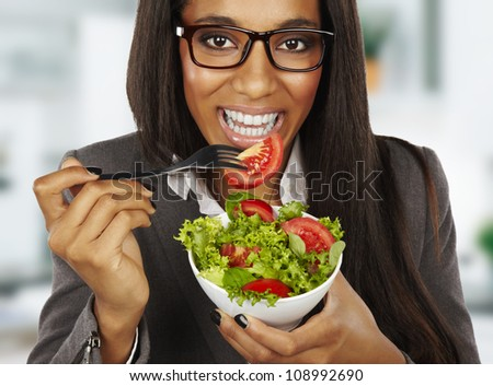 african happy businesswoman eating salad at office - stock photo