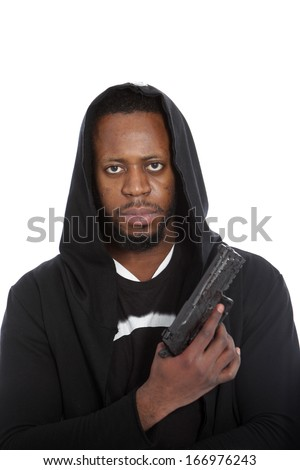 African hooligan or gangster wearing a black hooded top with a gun in his hand looking grimly at the camera in a threatening stance, isolated on white
