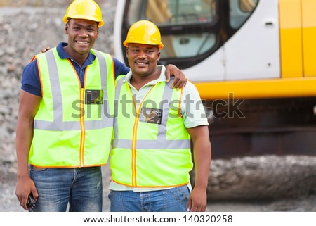 african industrial co-workers portrait in front of machine - stock photo