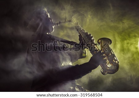 African jazz musician playing the saxophone. Yellow color - stock photo