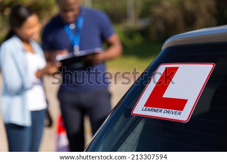 african learner driver and instructor behind a car - stock photo