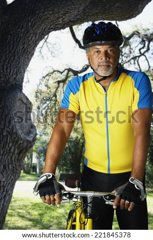 African male cyclist next to bicycle - stock photo