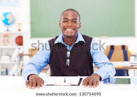 African male primary teacher sitting in classroom alone