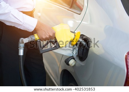 african male pumping gas at station