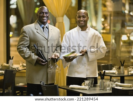 African male restaurant staff holding food and wine - stock photo