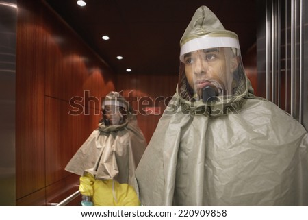 African man and woman in hazmat suits - stock photo