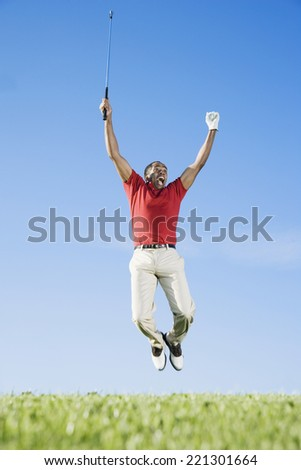 African man cheering on golf course - stock photo