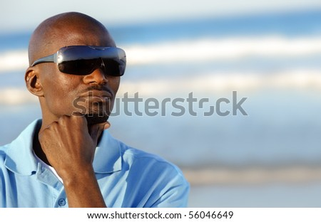 African man deep in thought at the beach - stock photo