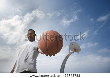 African man holding basketball - stock photo