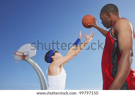 African man holding basketball away from nerd - stock photo