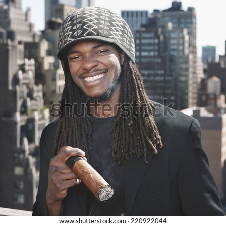African man holding large cigar - stock photo