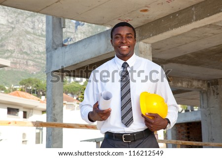 African man in a construction site holding his hard hat and building plans