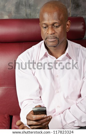 African man in pink shirt texting on mobile while sitting on red sofa - stock photo