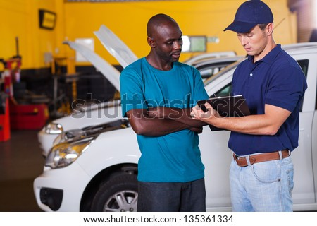 african man inside vehicle workshop with auto mechanic - stock photo