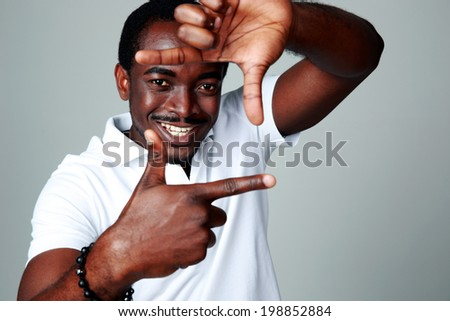 African man making frame sign with his hands on gray background