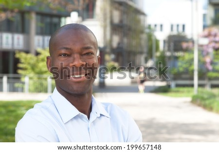 African man outside laughing at camera - stock photo