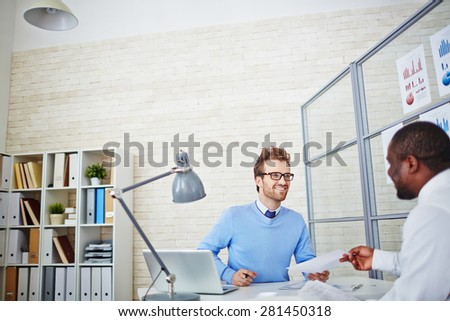 African man passing over his resume to employer in office - stock photo