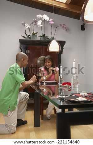 African man proposing to girlfriend - stock photo