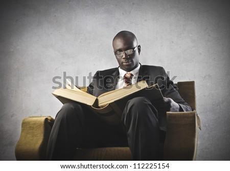 African man reading a book on an armchair - stock photo