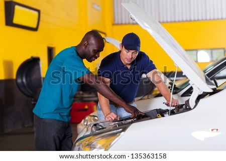african man showing auto mechanic his car problem inside workshop - stock photo
