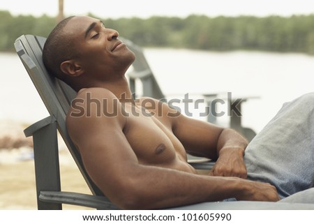 African man sitting in deck chair - stock photo