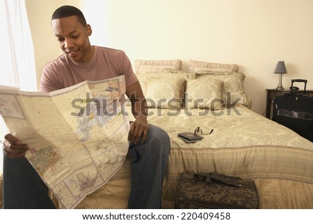 African man sitting on bed looking at map - stock photo