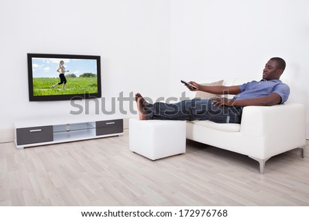 African Man Sitting On Sofa With Remote Holding In Hand - stock photo