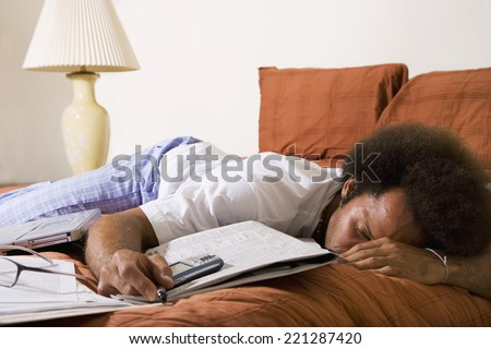 African man sleeping on bed - stock photo